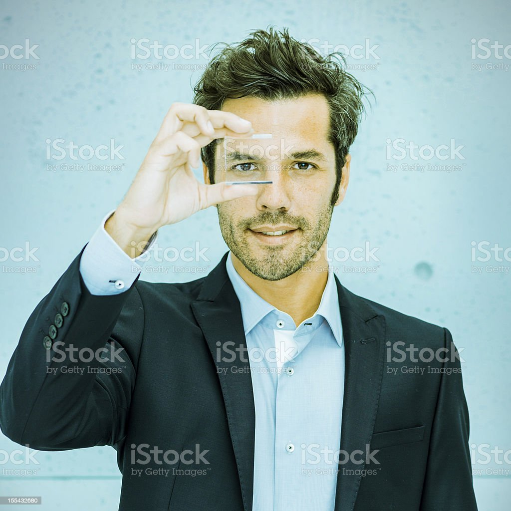 Businessman looking through a lens stock photo