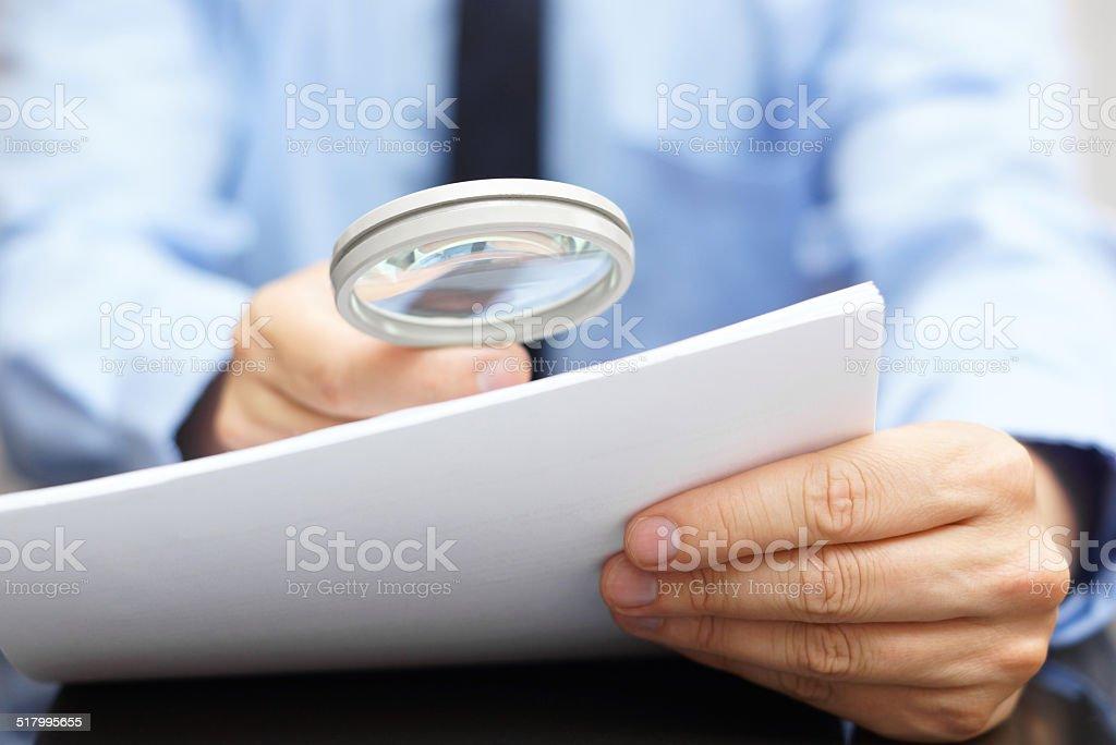 Geschäftsmann schaut durch ein Vergrößerungsglas, Vertrag Lizenzfreies stock-foto