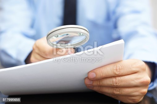 istock Businessman looking through a magnifying glass to contract 517995655