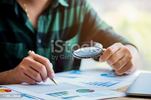istock Businessman looking through a magnifying glass to documents. Business assessment and audit. Magnifying glass on a financial report. Close-up Of Businessperson Checking Bills With Magnifying Glass.Concept of search. 1158238866