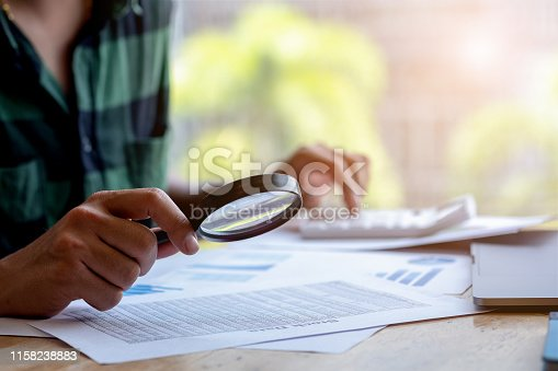 istock Businessman looking through a magnifying glass to documents. Business assessment and audit. Magnifying glass on a financial report. Close-up Of Businessperson Checking Bills With Magnifying Glass.Concept of search. 1158238883