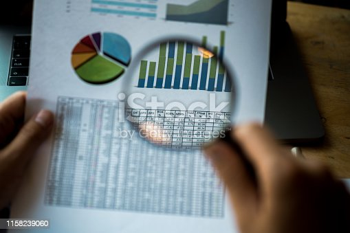istock Businessman looking through a magnifying glass to documents. Business assessment and audit. Magnifying glass on a financial report. Close-up Of Businessperson Checking Bills With Magnifying Glass.Concept of search. 1158239060