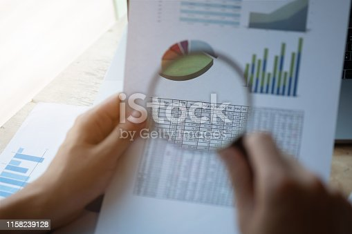 istock Businessman looking through a magnifying glass to documents. Business assessment and audit. Magnifying glass on a financial report. Close-up Of Businessperson Checking Bills With Magnifying Glass.Concept of search. 1158239128