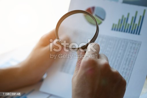 istock Businessman looking through a magnifying glass to documents. Business assessment and audit. Magnifying glass on a financial report. Close-up Of Businessperson Checking Bills With Magnifying Glass.Concept of search. 1158239148