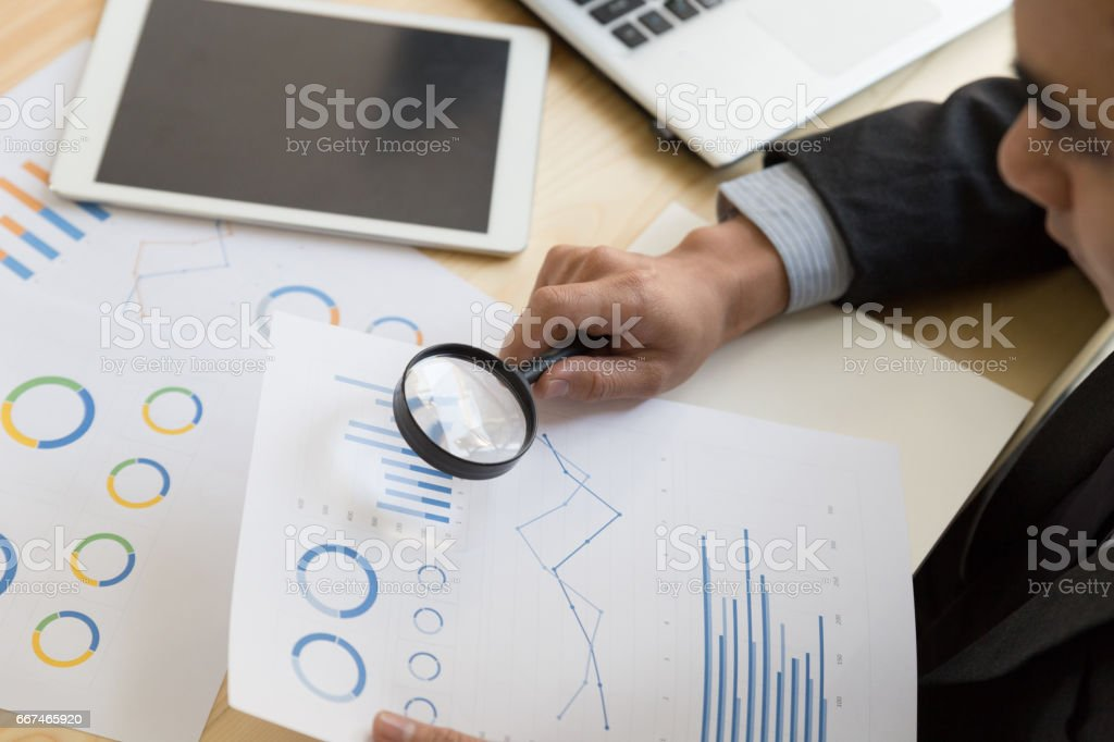 Businessman looking through a magnifying glass to documents stock photo