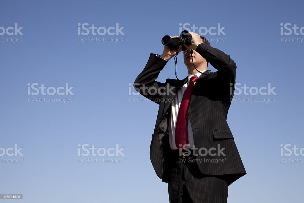 A businessman looking through a pair of binoculars  royalty-free stock photo