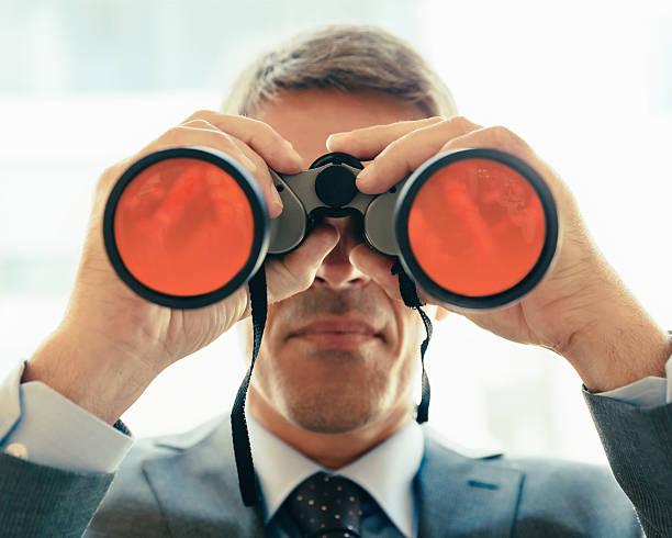 Homme d'affaires à la recherche par le biais de jumelles - Photo