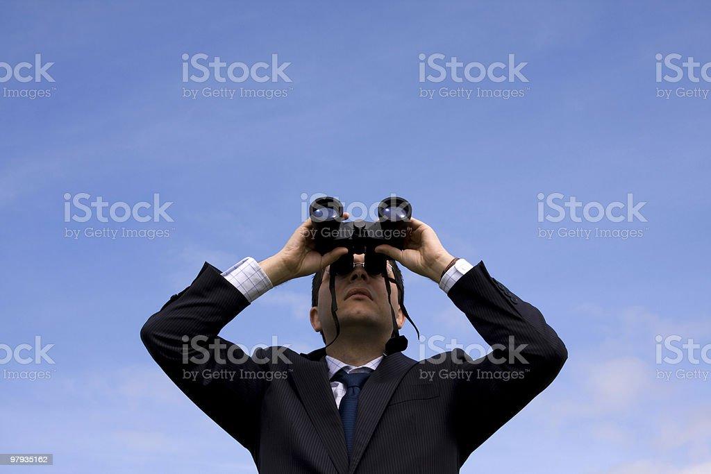 Businessman looking through binoculars royalty-free stock photo