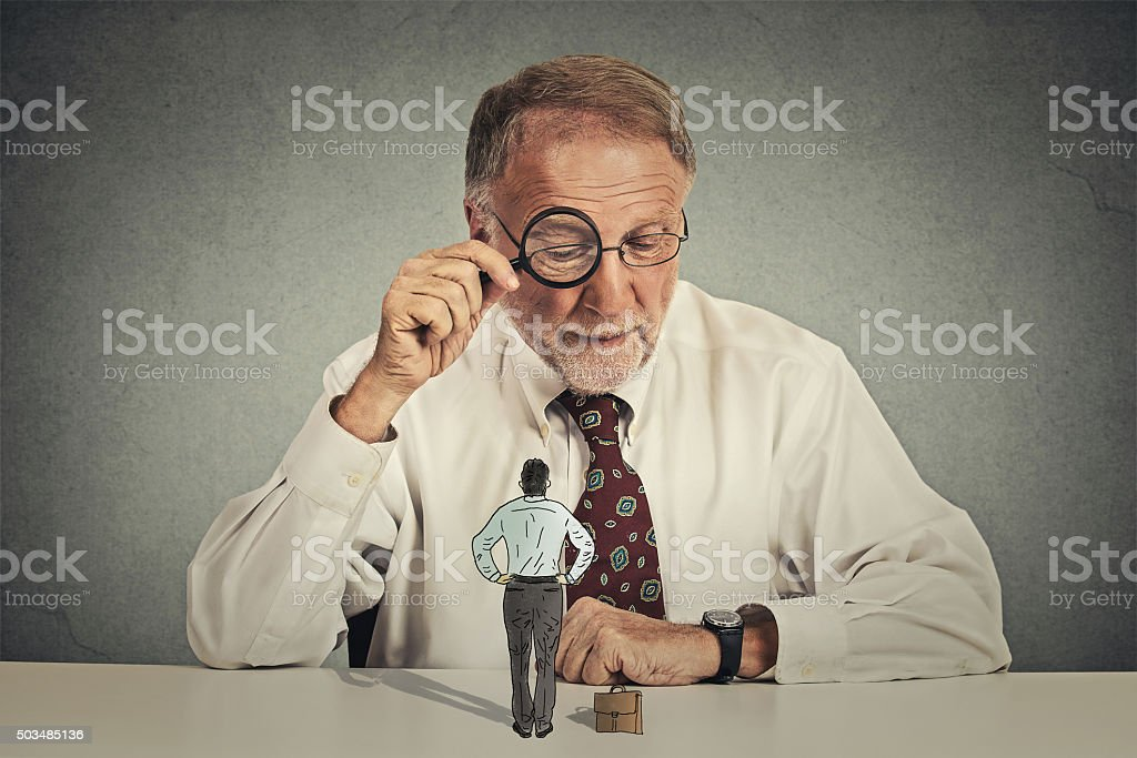 businessman looking through magnifying glass at employee stock photo