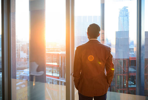 Businessman looking through office window in sunlight stock photo