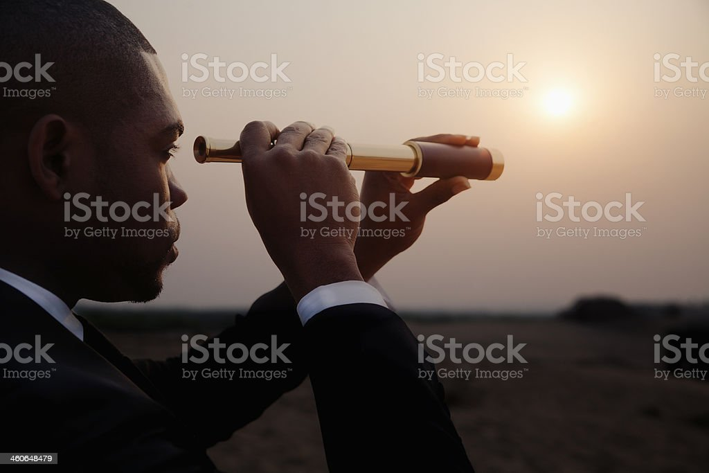 Businessman looking through spyglass in middle of the desert stock photo