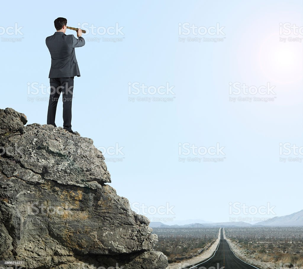 Businessman looking through spyglass in the desert stock photo