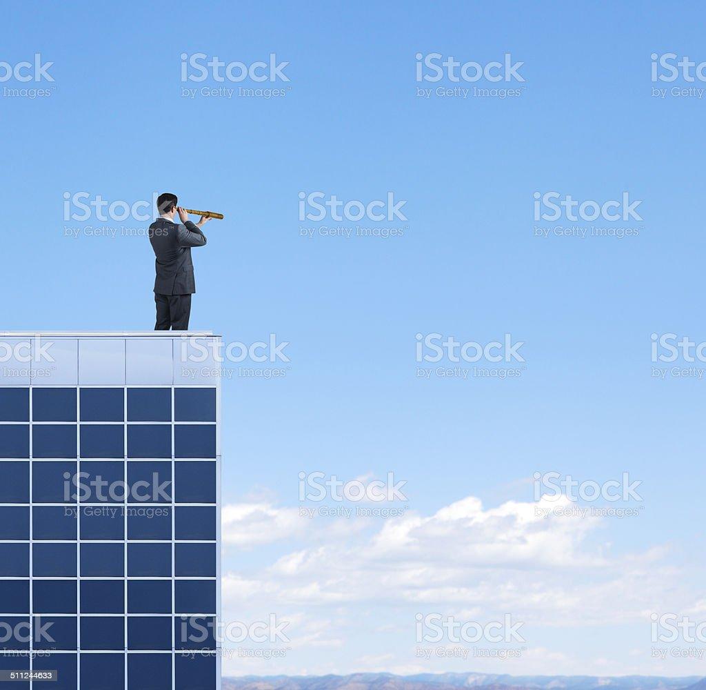 Businessman looking through spyglass on top of bskyscraper stock photo