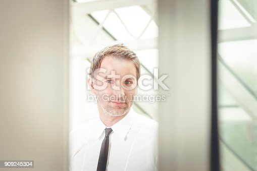825082848istockphoto businessman looking through the door at the office 909245304