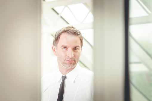 825082848 istock photo businessman looking through the door at the office 909245304
