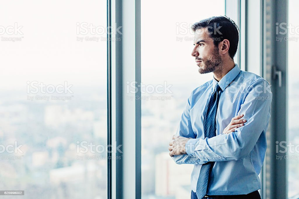 Businessman looking through the window stock photo