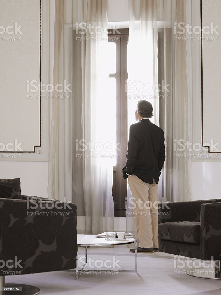 Businessman looking through window in hotel lobby royaltyfri bildbanksbilder