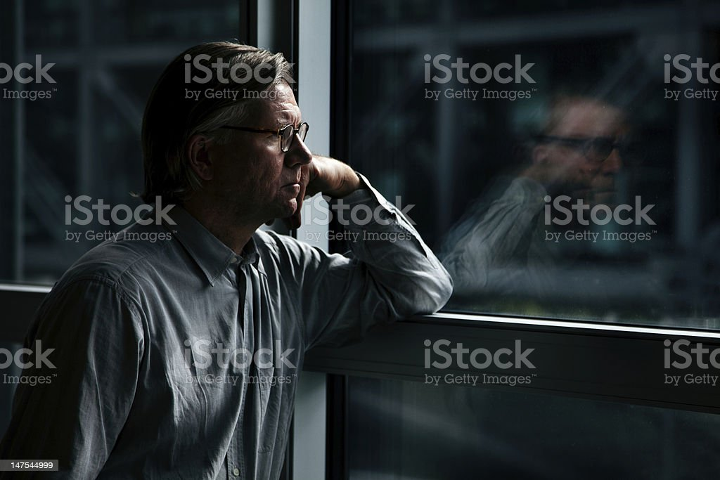 Businessman looking through window stock photo