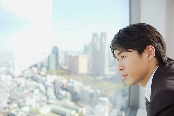 Businessman looking through window  only japanese stock pictures, royalty-free photos & images