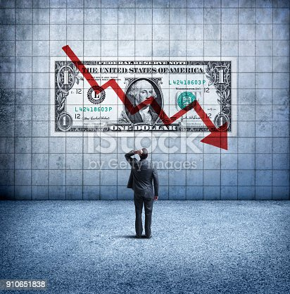 A rear view of a concerned businessman as he places his hand on his head and looks up at a U. S. One Dollar bill coupled with a downward trending arrow and chart on the wall in front of him. This image illustrates the concept of a falling, or weakening U.S. dollar.