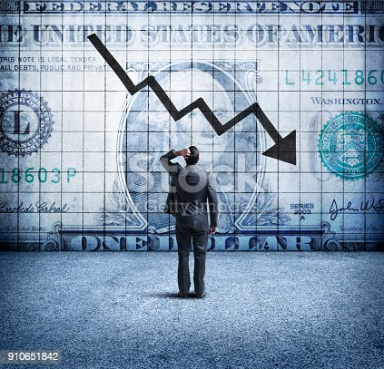 A rear view of a concerned businessman as he places his hand on his head and looks up at a U.S. One Dollar bill coupled with a downward trending arrow and chart on the wall in front of him. This image illustrates the concept of a falling, or weakening U.S. dollar.