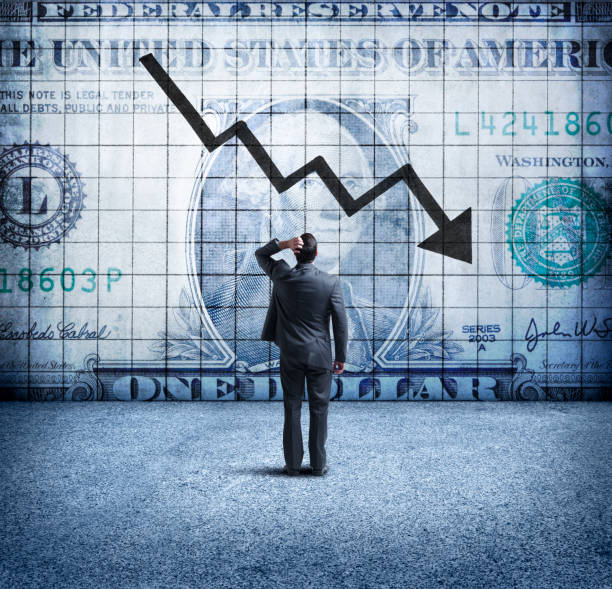 businessman looking up at a chart that indicates a falling u.s. dollar - deterioration stock pictures, royalty-free photos & images