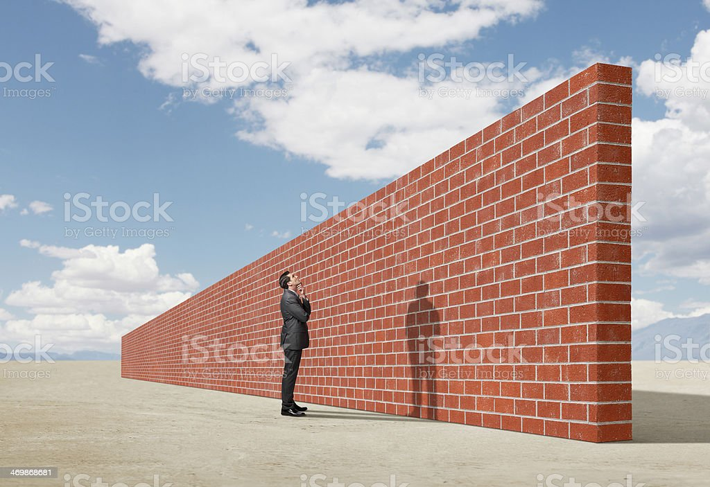 Businessman looking up at brick wall in middle of desert stock photo
