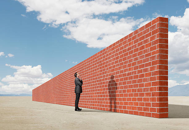 Businessman looking up at brick wall in middle of desert A man stands with his arms folded in front of him as he looks up towards a long and tall brick wall. The brick wall represents an impediment to his progress.  He is contemplating a solution to getting around the wall.  The wall is oddly placed in the middle of a desert salt flat . boundary stock pictures, royalty-free photos & images