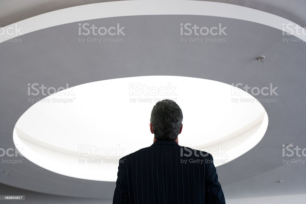 Businessman looking up at ceiling light stock photo
