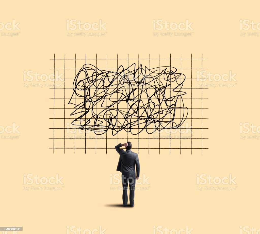 Businessman Looking Up At Chart Showing Unpredictable Moves A businessman places his hand on his head in confusion as he looks up at a large chart that shows unpredictable sales or performance trends. Adult Stock Photo