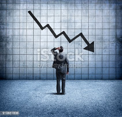 A rearview of a concerned businessman as he places his hand on his head and looks up at a downward trending arrow on a chart on the wall in front of him.