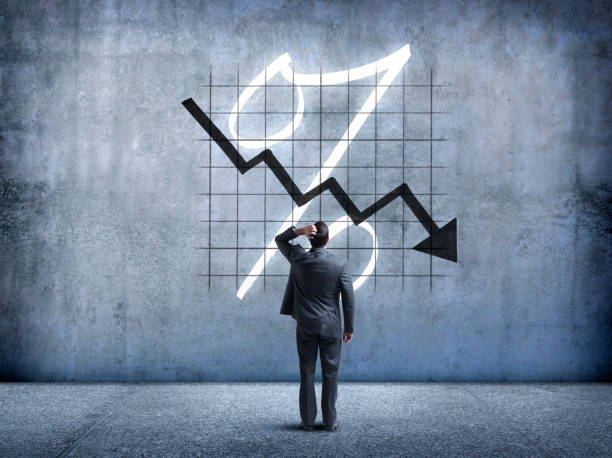 Businessman Looking Up At Falling Interest Rates A businessman places his hand on his head as he looks up and is perplexed by a chart indicating falling interest rates. interest rate stock pictures, royalty-free photos & images