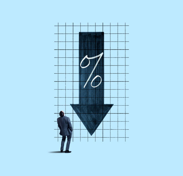 Businessman Looking Up At Falling Interest Rates stock photo