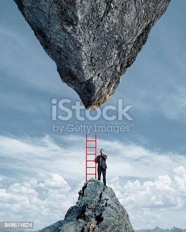 A businessman stands on top of a mountain peak holding a red ladder as he looks up at the impossible situation of having to climb to a much larger inverted mountain peak directly above him.