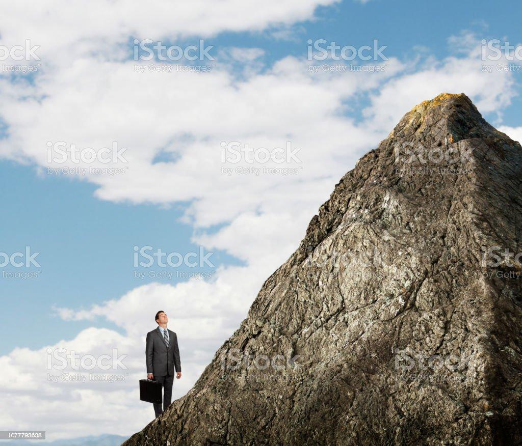 Businessman Looking Up At Mountain Peak stock photo