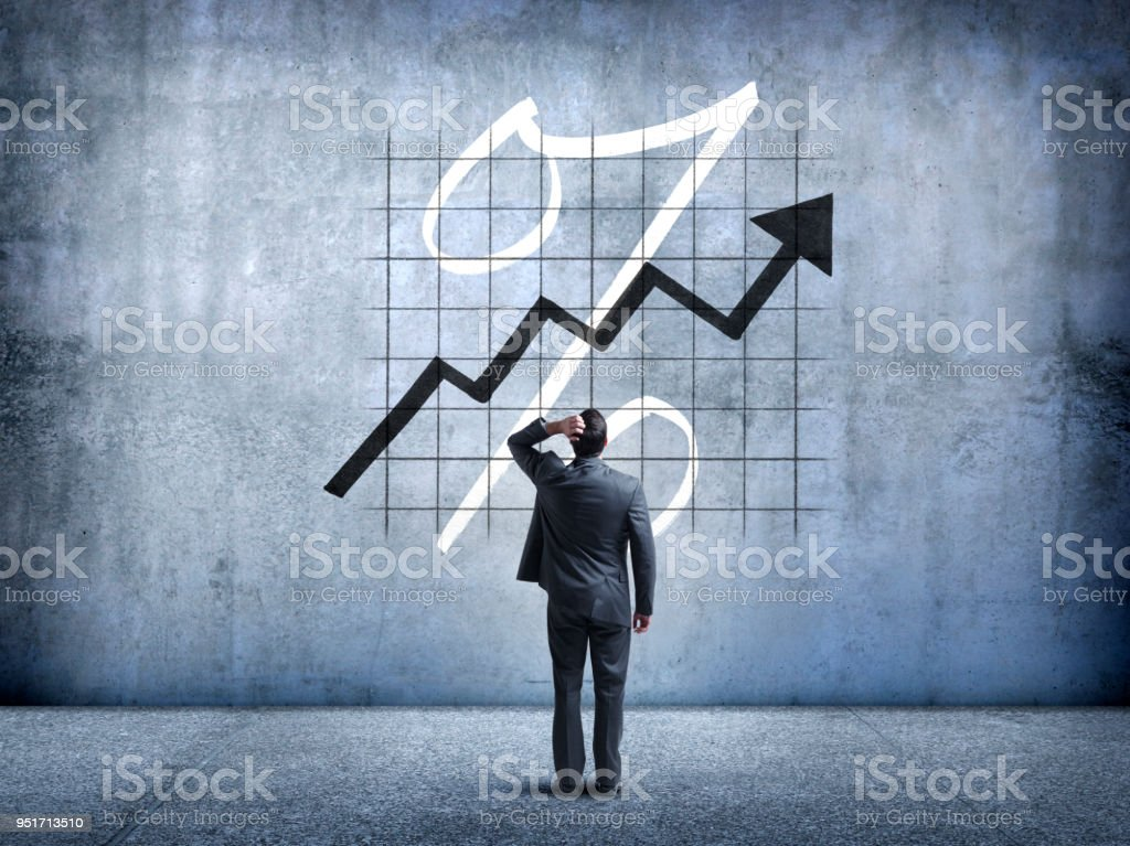 Businessman Looking Up At Rising Interest Rates stock photo