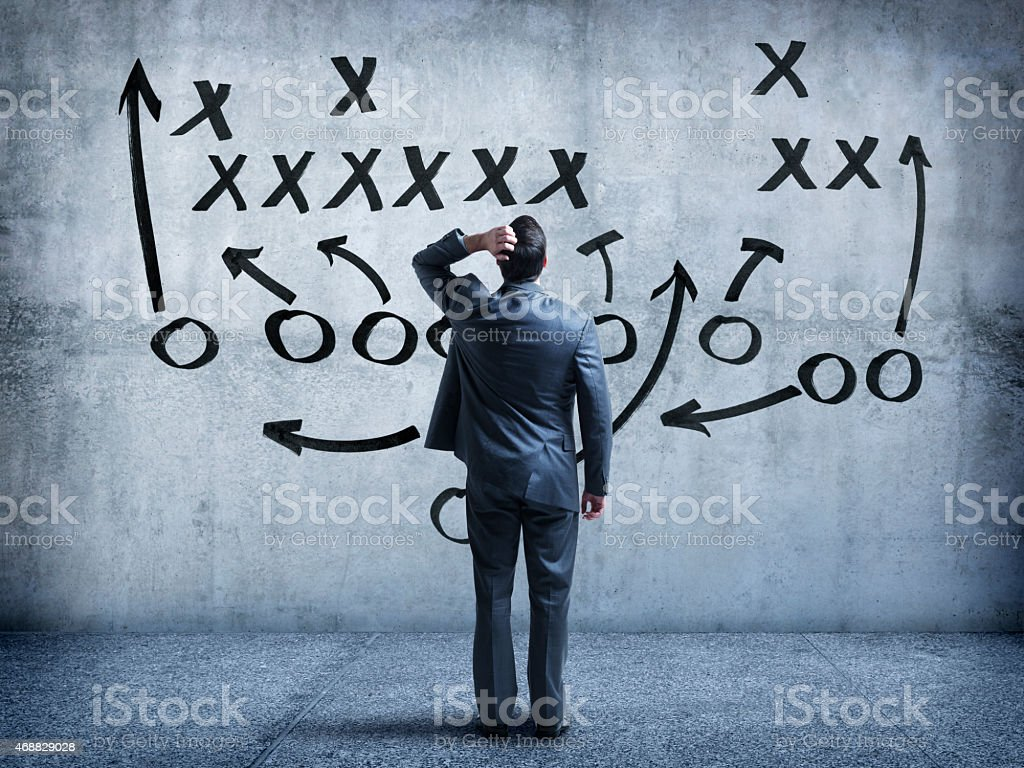 Businessman looking up at strategy diagram on wall stock photo