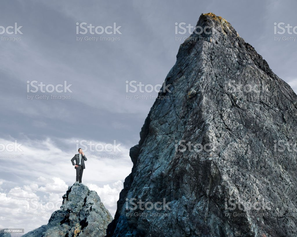 Businessman Looking Up At Tall Mountain stock photo