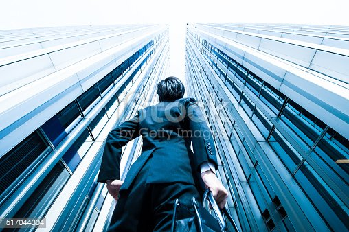 istock Businessman looking up at the high building, low angle 517044304