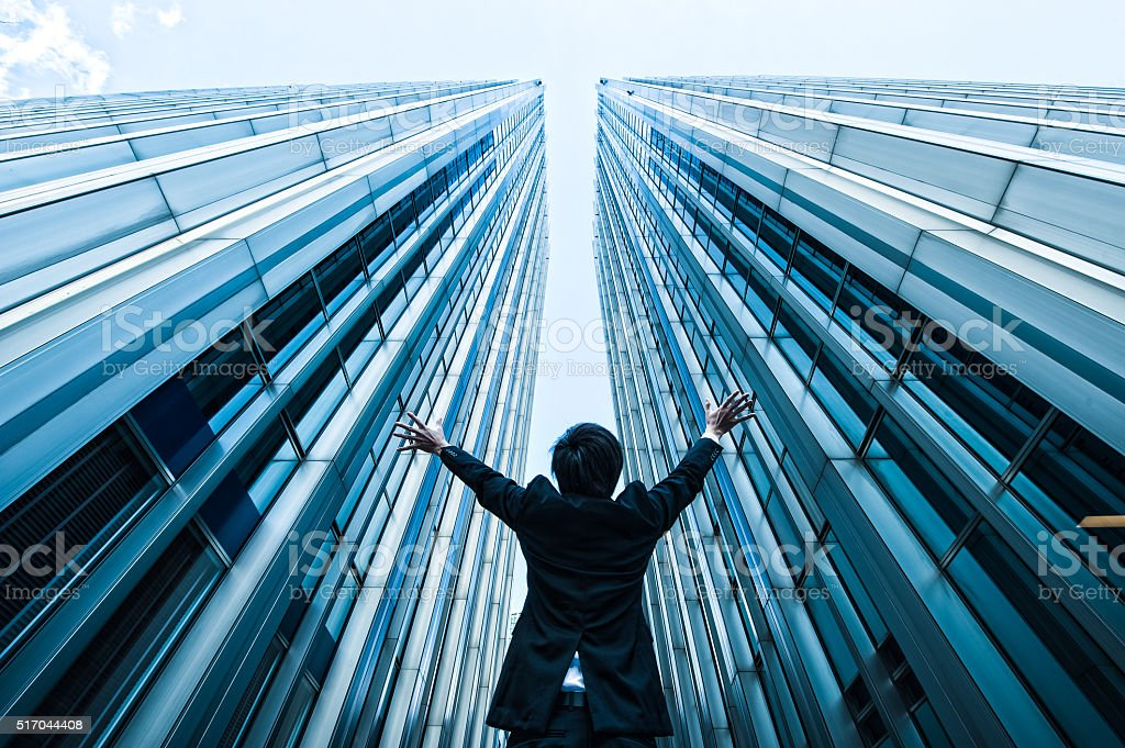 Businessman looking up at the high building, low angle stock photo