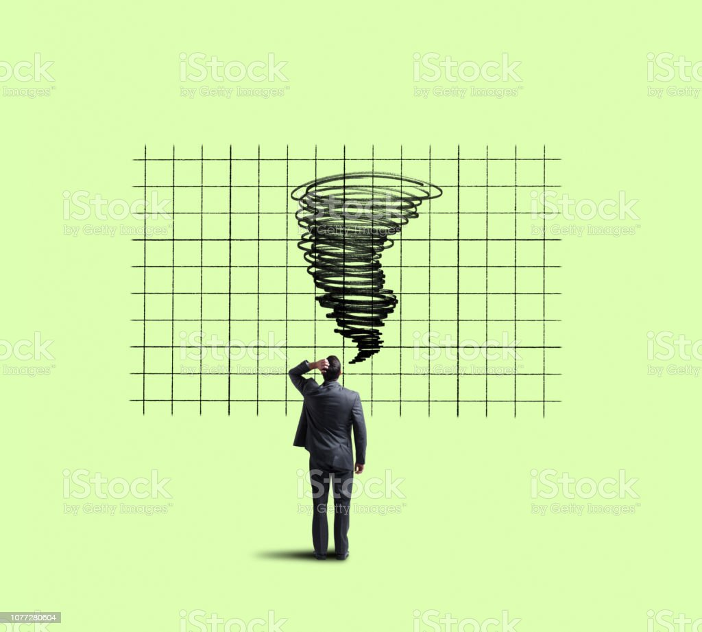Businessman Looking Up At Tornado On Chart stock photo