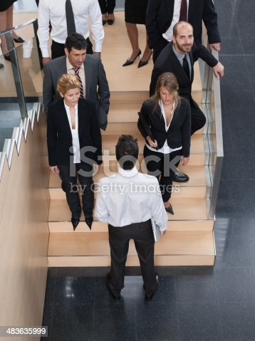 483635979 istock photo Businessman looking up busy office staircase 483635999