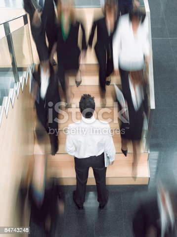 483635979 istock photo Businessman looking up busy office staircase 84743248