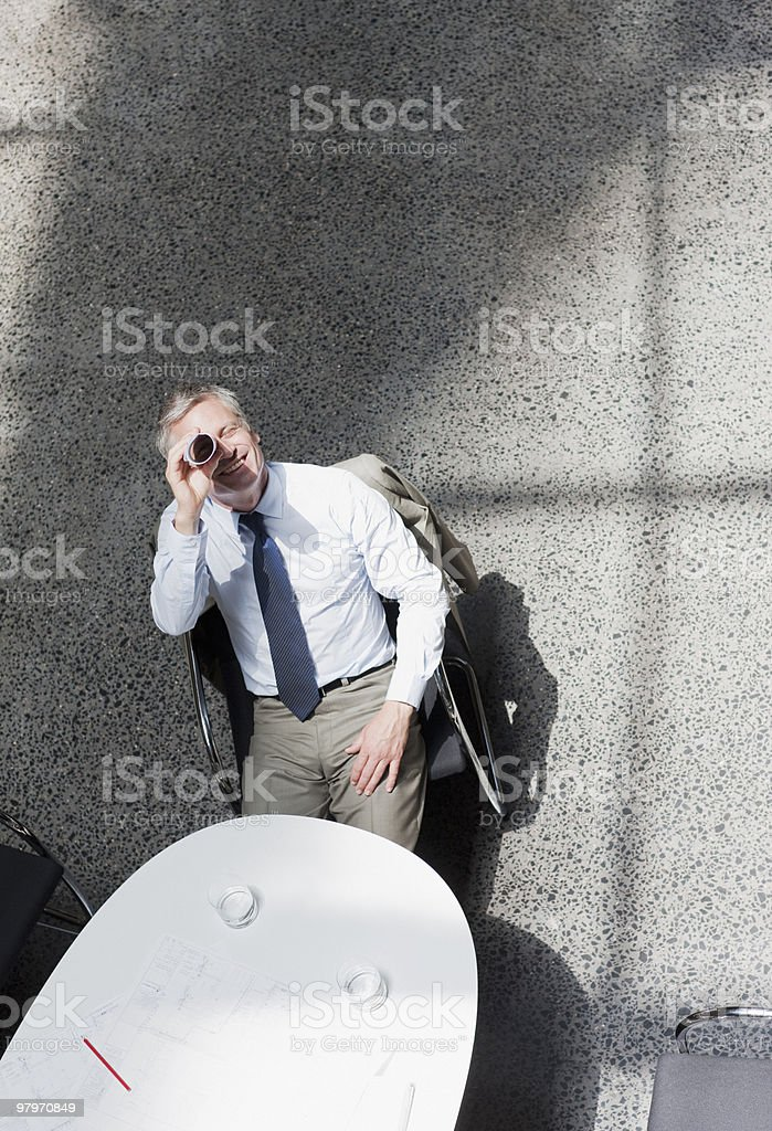 Businessman looking up through rolled up paperwork royalty-free stock photo