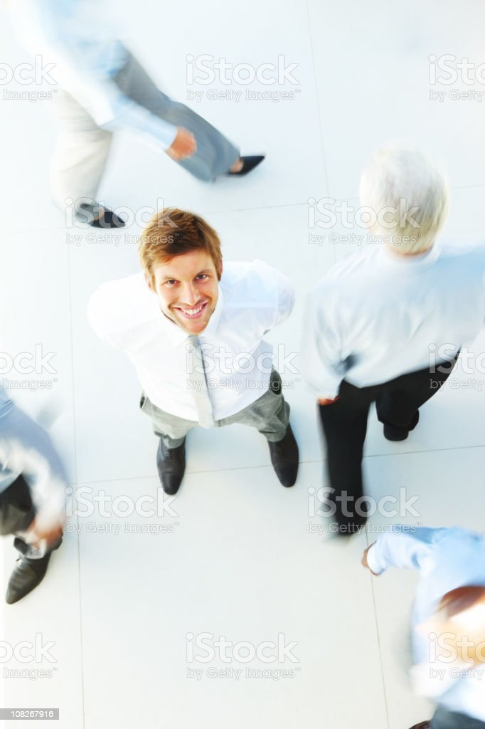 Businessman looking upward and business people moving around him royalty-free stock photo