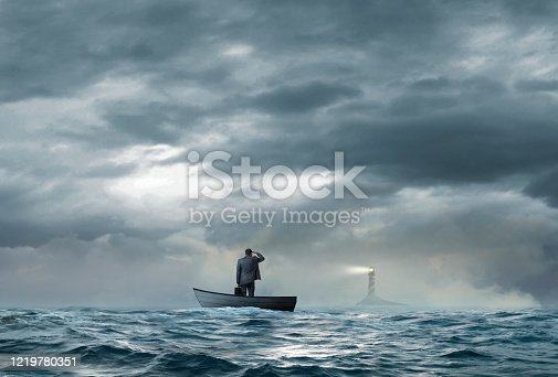 A beacon from a lighthouse beckons a stranded businessman as he stands in a small boat that floats under an ominous sky and choppy waters.