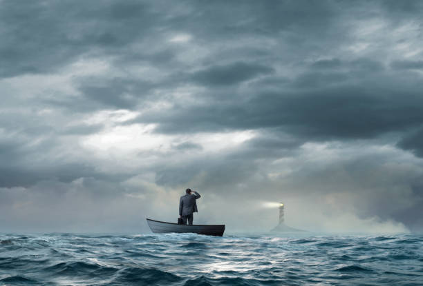 Businessman Looks At Lighthouse While Stranded On Boat A beacon from a lighthouse beckons a stranded businessman as he stands in a small boat that floats under an ominous sky and choppy waters. aground stock pictures, royalty-free photos & images