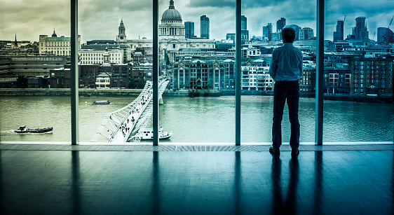 Rear view, low angle image of a businessman with hands on hips, looking out over the architecture of the city of London. We can see the urban metropolis of the capital city of England, with key landmarks such as St Pauls Cathedral and an array of famous skyscrapers. The image has a cold blue feel to it, and there is lots of room for copy space. Horizontal colour image.