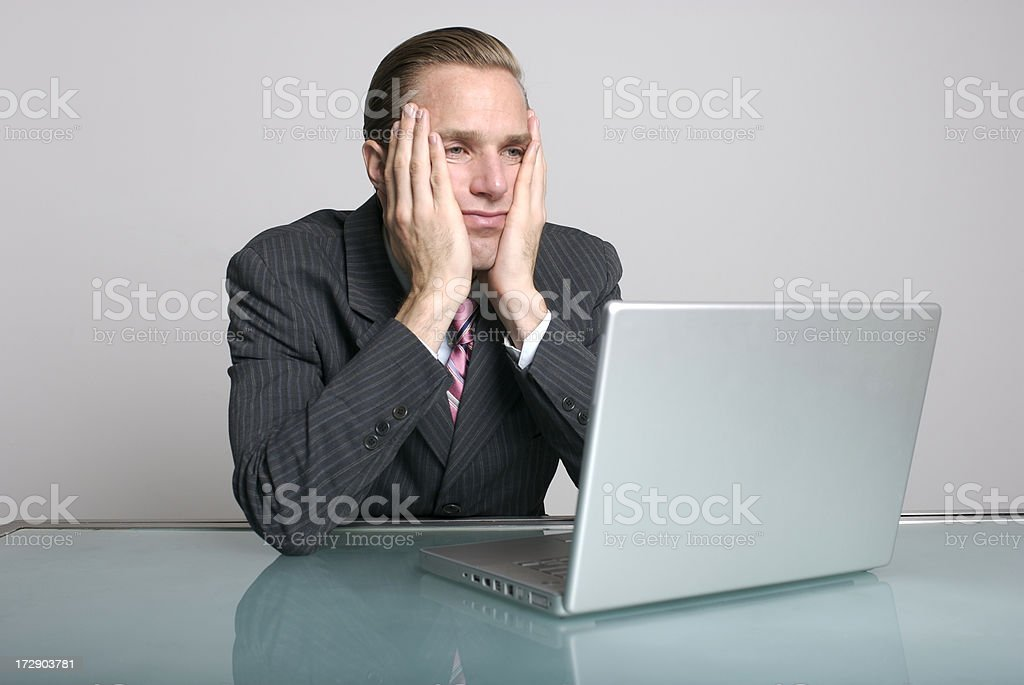 businessman looks bored in front of laptop computer at desk stock