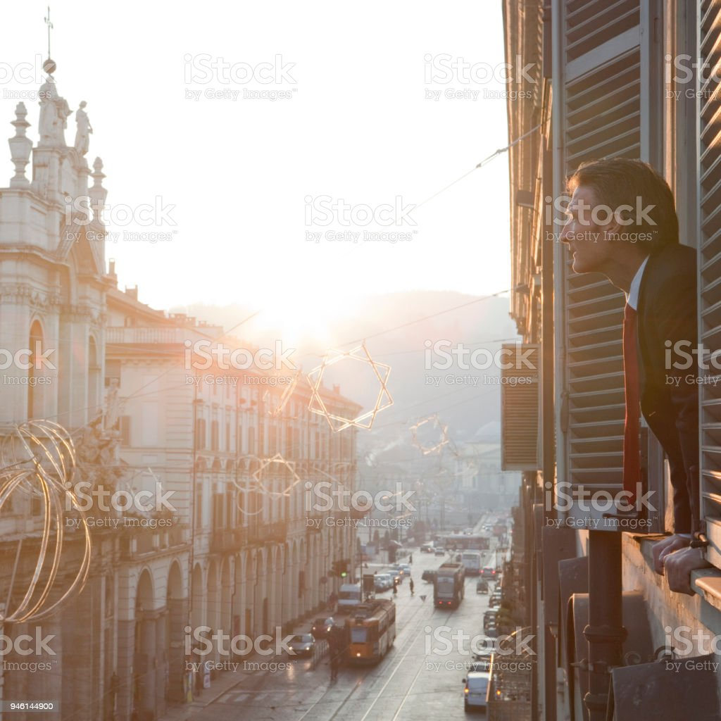 Businessman looks out of window above city street. stock photo
